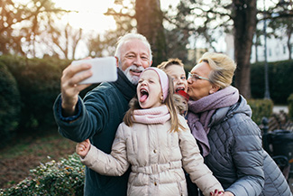 Happy grandparents taking selfie with grandchildren